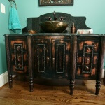 Black vanity with a rub through finish and vessel sink