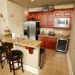 small kitchen with bar area and wine cooler
